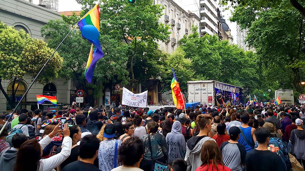Muita gente e muitas bandeiras do arco-íris