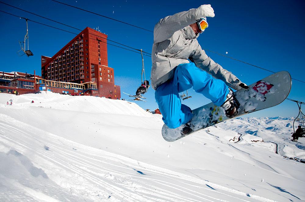 Snowboarder saltando em frente ao Hotel Puerta Del Sol, no Valle Nevado - Foto: Divulgação